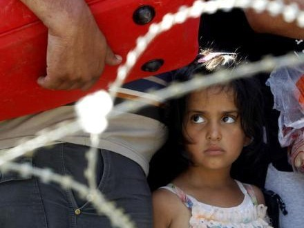 A migrant girl looks on from behind barbed wire while waiting with her family to enter into Macedonia from Greece, on the border line between the two countries, near southern Macedonia's town of Gevgelija, on Wednesday, Aug. 26, 2015.  Some thousands of migrants have poured into Macedonia and boarded trains and busses that are taking them a step closer to the European Union. (ANSA/AP Photo/Boris Grdanoski)